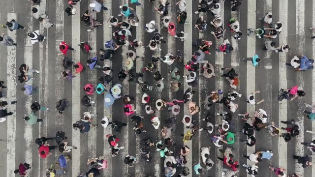 Aerial view of pedestrians walking across with crowded traffic