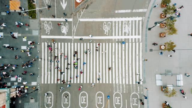 Luftaufnahme von Fußgängern, die mit überfülltem Verkehr querlaufen – Video