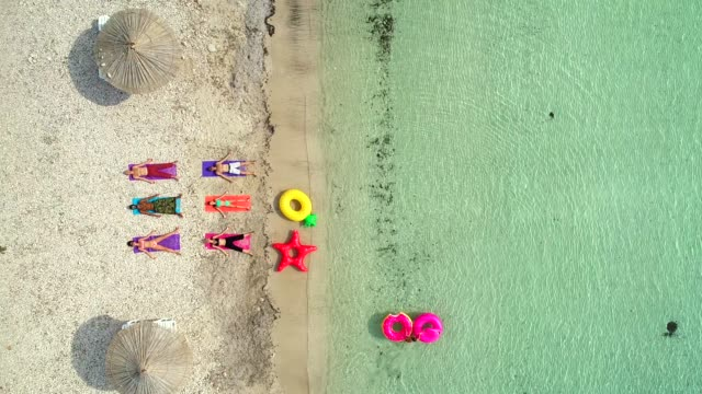 Aerial view of people lying in yoga pose with inflatables.