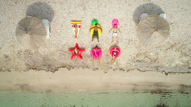 vídeos de stock, filmes e b-roll de vista aérea de pessoas no grandes colchões infláveis na praia. - inflável