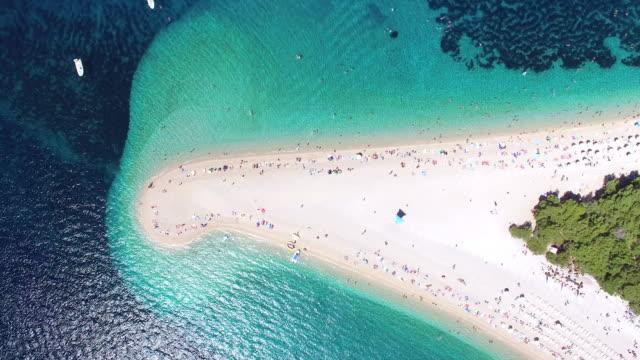 aerial view of people sunbathing on a sandy beach on the island of brac, croatia - хорватия стоковые видео и кадры b-roll