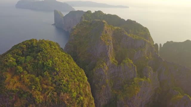 luftaufnahme von phi phi, maya strand mit blau türkisfarbenem meerwasser, berghügeln und tropischen grünen waldbäumen bei sonnenuntergang mit andamanenmeer auf phuket insel im sommer, thailand in reisereise. natur. - phuket stock-videos und b-roll-filmmaterial