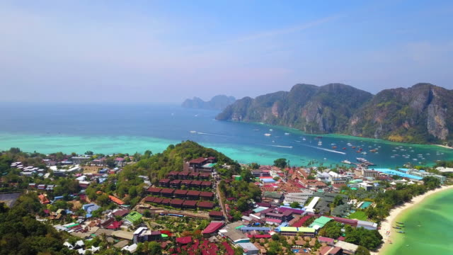 aerial view of phi phi, maya beach with blue turquoise seawater, mountain hills, and tropical green forest trees at sunset with andaman sea in phuket island in summer, thailand in travel trip. nature. - phuket video stock e b–roll
