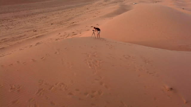 aerial view of photographer on top of dunes in desert at sunset - paesi del golfo video stock e b–roll