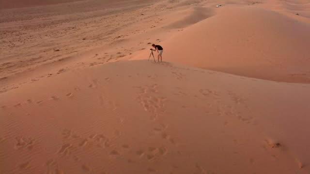 aerial view of photographer on top of dunes in desert at sunset - fotografika filmów i materiałów b-roll