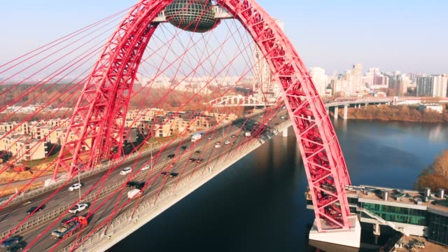 aerial view of picturesque bridge which crosses the moscow river in moscow. cars traffic on cable-stayed bridge of red color at day time. - rzeka moskwa filmów i materiałów b-roll