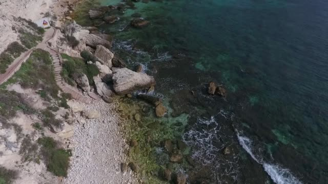 Aerial view of pieces of rock lying in the sea near the shore of the island of Corsica