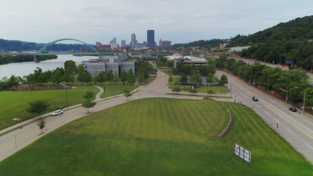 Aerial View of Pittsburgh Skyline and Office Park A rising aerial view of a technology office park in Pittsburgh, Pennsylvania on an overcast summer day. The city skyline and Birmingham Bridge in the distance. office park stock videos & royalty-free footage