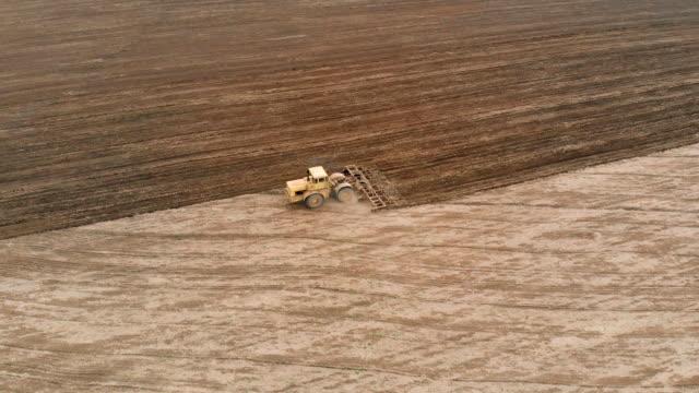 Flygbild av plöjning mark med stor kraftfull traktor med kulör före sådd video