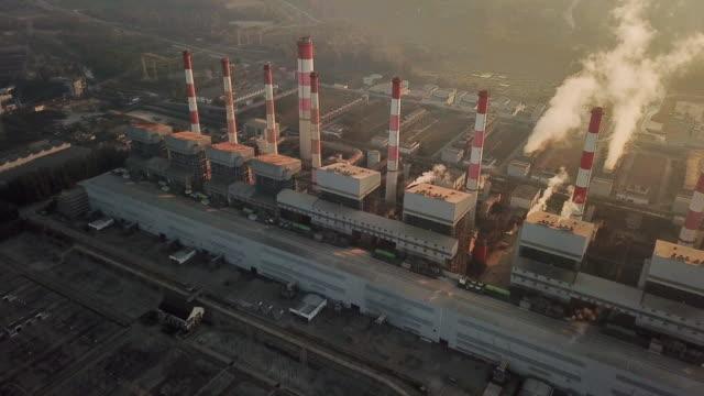Aerial view of Power plant with smokestacks smoking , Sunset time