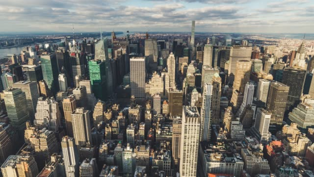 t/l ws ha tu aerial view of prosperous cityscape changing in sunlight / manhattan, nyc - манхэттен стоковые видео и кадры b-roll
