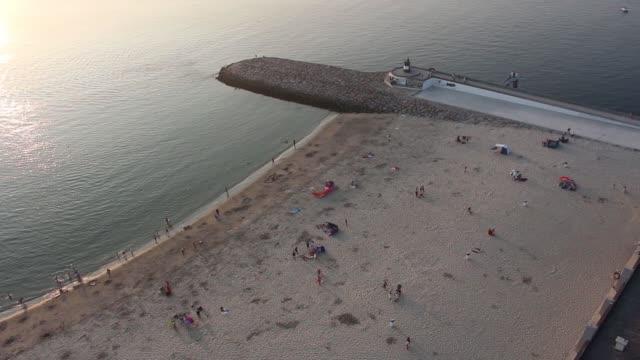 vídeos de stock e filmes b-roll de aerial view of quiet beach with calm ocean and few people. barra beach from aveiro, portugal. - aveiro