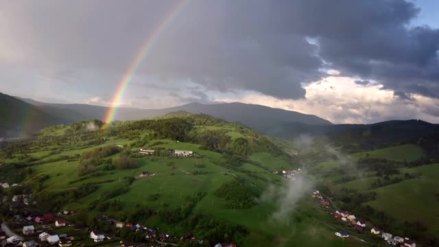 Aerial view of rainbow over green rural countryside in sunny rainy evening
