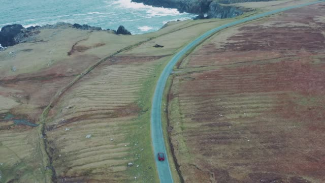 aerial view of red car moving on beautiful curved coastal road. Ireland, Achill Island aerial view of red car moving on beautiful curved coastal road. Ireland, Achill Island car rental stock videos & royalty-free footage