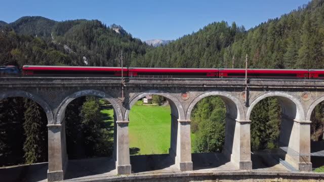 vídeos de stock, filmes e b-roll de vista aérea de passeios vermelhos do trem no viaduto famoso de kalte rinne na estrada de ferro semmering histórica (semmeringbahn), áustria mais baixa. - áustria