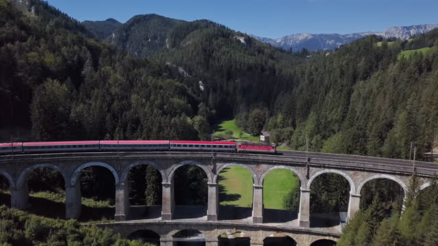 Aerial view of red train rides on famous Kalte Rinne Viaduct on historical Semmering railway (Semmeringbahn), Lower Austria.