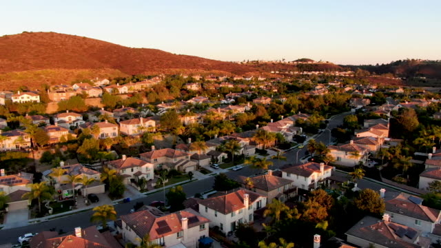 vídeos de stock e filmes b-roll de aerial view of residential modern subdivision during sunset - encosta