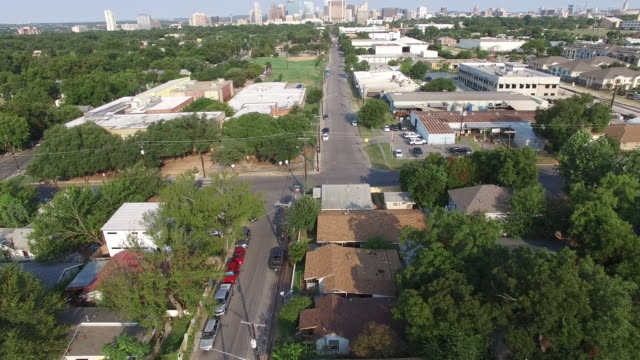 Aerial view of residential neighborhood surrounded with lot of greenery and buildings in background - Austin, Texas, USA video