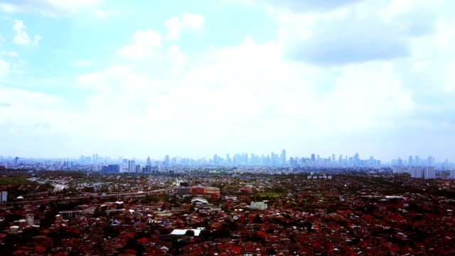 Aerial view of residential with jakarta skyscrapers in distance Aerial view of residential with jakarta, Indonesia  skyscrapers in distance. Shot in 4K from a drone jakarta stock videos & royalty-free footage