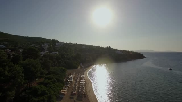Aerial view of resort with sunbeds on the shore in bright sun light, Greece video