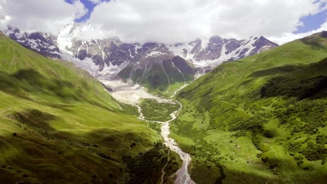 aerial view of river in mountain valley at the foot of mt. shkhara. georgia. - trekking sul ghiaccio video stock e b–roll