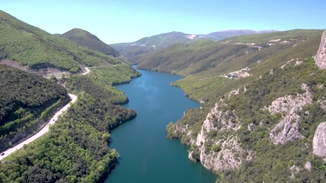 Aerial view of river in valley and country road on the side, Veria Greece, motion in front of a drone