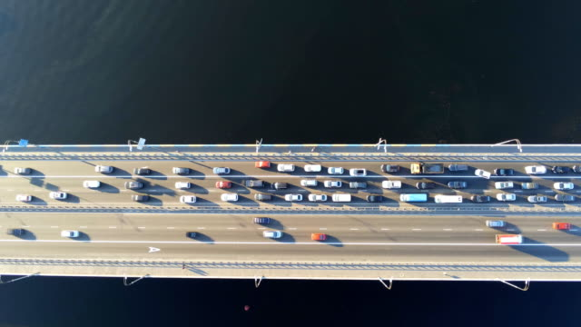 vídeos de stock e filmes b-roll de aerial view of road bridge across river with heavy traffic jam in one direction. rush hour with mash and overloading of road infrastructure. - ponte