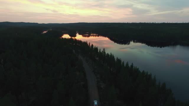 flygfoto över vägen i skogen i skymningen. bil som kör på grusväg - pine forest sweden bildbanksvideor och videomaterial från bakom kulisserna