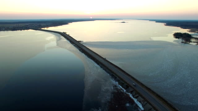 4K. Aerial view of road in the frozen water with moving cars on sunset, winter top view. video