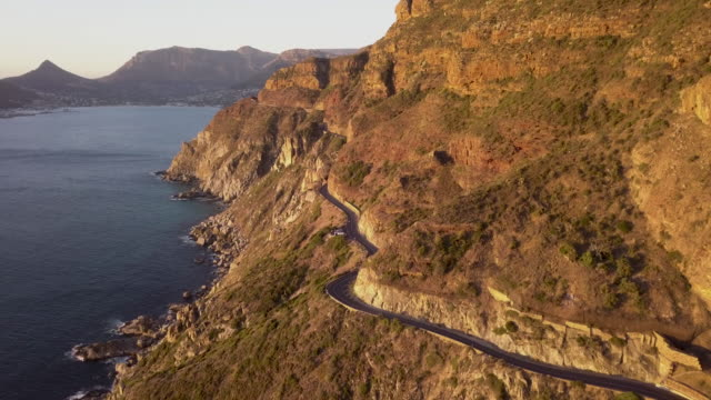 Aerial view of road on a cliffside coastline Aerial view of rocky coastline at Chaopmans Peak, Cape Town, South Africa cape town stock videos & royalty-free footage
