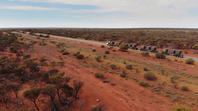 Aerial View of Road Train in the Australian Outback Very large mining truck (road train) traveling the Australian desert of Australia  (Aerial View, Drone Shot). australia stock videos & royalty-free footage