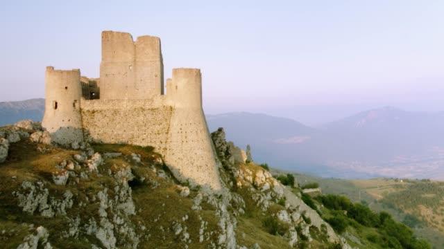 vídeos de stock, filmes e b-roll de vista aérea do castelo de rocca calascio no ocaso - castelo