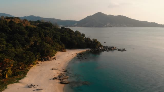 Aerial view of rock cliff and coast, sea water in sunset. Flying above mountains and beach. Aerial top view.