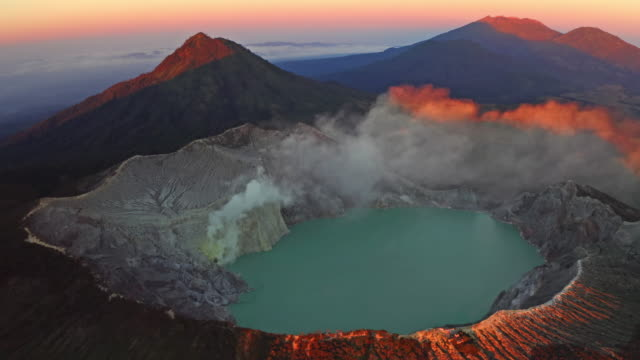 Aerial view of rock cliff at Kawah Ijen volcano with turquoise sulfur water lake at sunrise. Panoramic view at East Java, Indonesia. Natural landscape background.