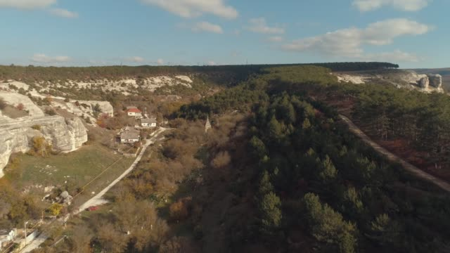 Aerial view of rocky cliffs, forest and small village against blue sky. Shot. Early autumn landscape