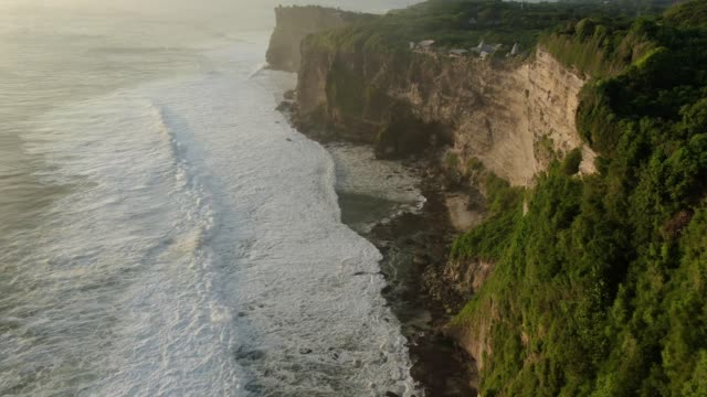 Aerial view of rocky coast with big waves at sunset.