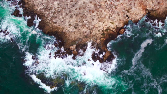 Aerial view of rocky coastline and crashing waves against cliffs video