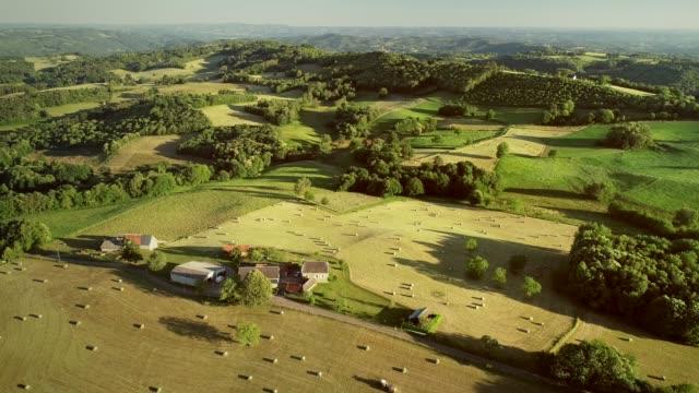 aerial view of rolling hills and straw bales. - francja filmów i materiałów b-roll