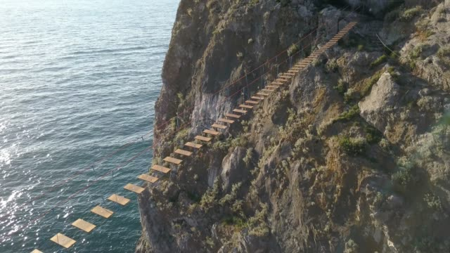 aerial view of rope bridge between the rocks over the sea and danger waves and stones
