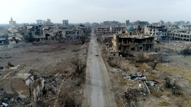 Aerial view of ruined Deir Ez-Zor after the war. Destroyed buildings everywhere. Destroyed city of Deir Ez-Zor in Syria since the war of 2014 - 2017. Buildings with no people in a damaged city. Aerial view with a drone of a destroyed Deir Ez-Zor because of terrorism. War years in Syria. A lot of dust and trash in all the city. syria stock videos & royalty-free footage