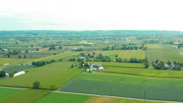 Aerial View of Rural Farmland In Pennsylvania with Barns, Silos, Corn Fields and Rolling Hills