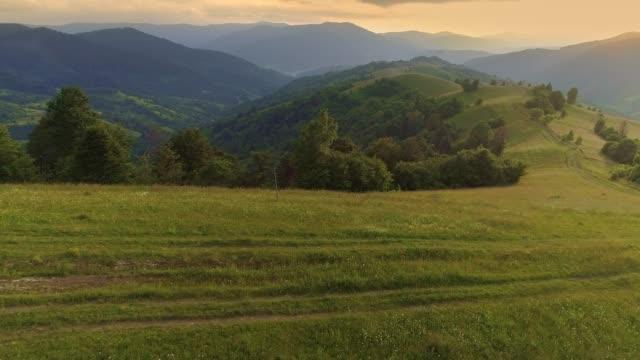 flygfoto över landsväg längs åsen på green hill. berg och ängar täckta med blommor och grönska i solnedgången strålar. vandring, ekoturism koncept under isolering pandemi period - bergsrygg bildbanksvideor och videomaterial från bakom kulisserna