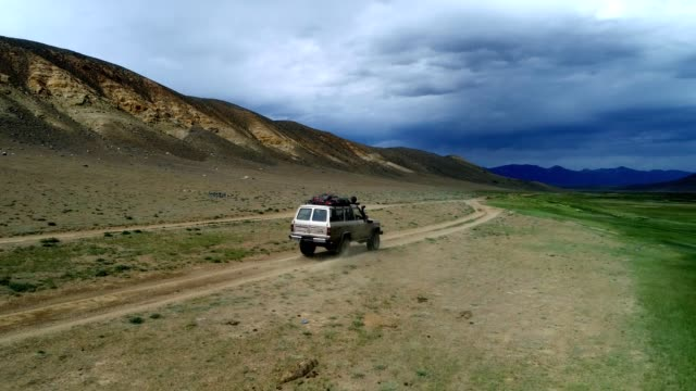 4K aerial view of safari vehicle driving on sand track road in the Altay Mountain