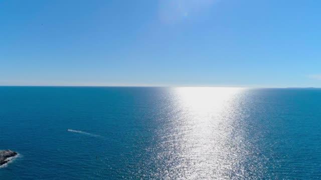 flygfoto över segelbåt i det blå havet. bara en båt eller yacht i det djupblå havet. 4k - vattenlandskap bildbanksvideor och videomaterial från bakom kulisserna