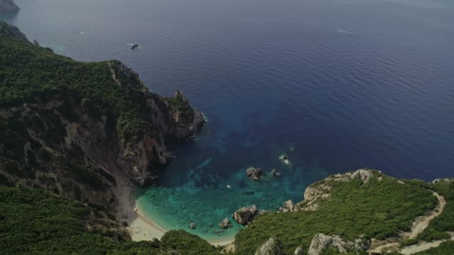 Aerial view of sandy wild beach of the turquoise water washing the rocky shoreline of  Corfu island in the Mediterranean