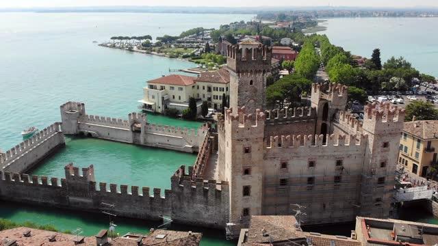 veduta aerea del castello scaligero, della città e della penisola di sirmione - lombardia video stock e b–roll