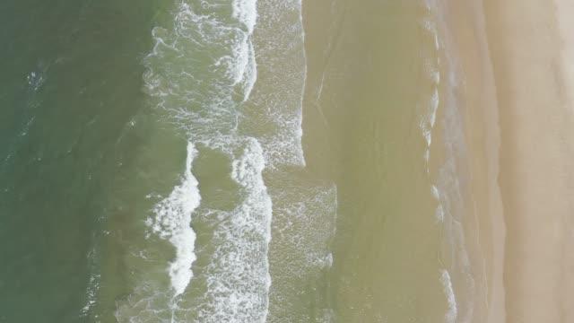 vídeos de stock e filmes b-roll de aerial view of sea or ocean surf wave. foamy ocean waves rolling and coming on a sand beach. laem mae phim beach - transatlântico
