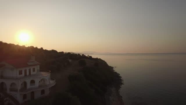 海、水辺の道、夕暮れ、ギリシャの畑の風景の空撮 - ヴィラ点の映像素材/bロール