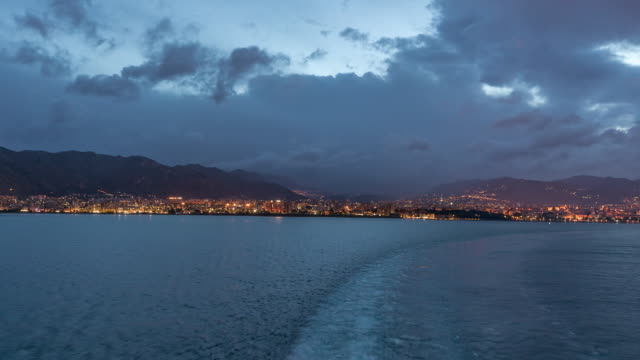 Aerial view of sea with wawes and port from ship sailing in the open sea timelapse Aerial view of sea with wawes and port from ship sailing in the open sea timelapse at evening after sunset. Shore of Palermo, Italy recreational boat stock videos & royalty-free footage