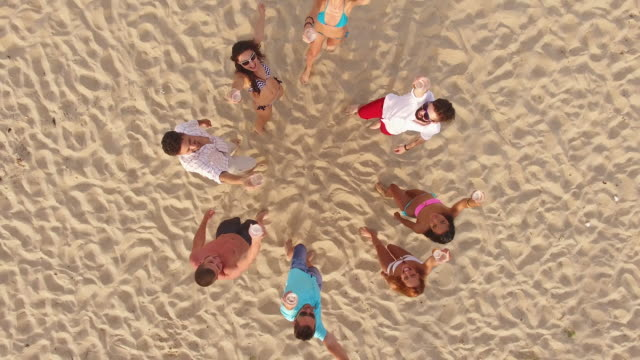 4K Aerial view of seaside and friends drinking beer on beach video